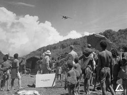 A plane flies overhead on the set of New Guinea Patrol