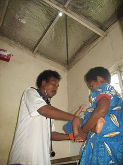 Doctor helping woman in PNG Aid Post