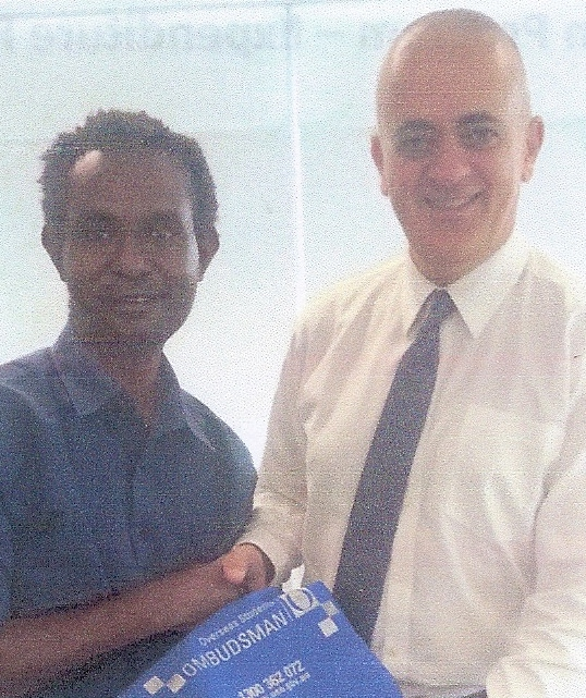 Martyn Namorong receives a gift from George Masri, Australia's Acting Deputy Ombudsman
