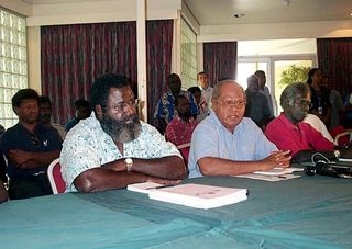 John Momis, pictured (centre) between former President Joseph Kabui and his wartime enemy, Joel Banam, in 2001 (AAP)