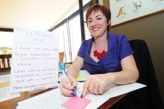 A silent Kerrie Phipps writes a post-it note during an appointment (Louise Donges)