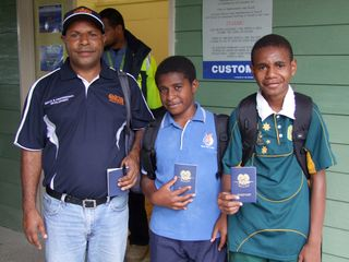 13-year olds, Cyril Bineng (centre) and Oscar Nori with OTML's James Yore at Tabubil International Airport awaiting their flight to Cairns