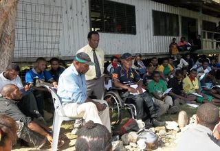 Mathias Kin (on chair) and Francis Nii (in wheelchair) talking to students and teachers at Ku Secondary School. Standing is school principal Ware Mukale