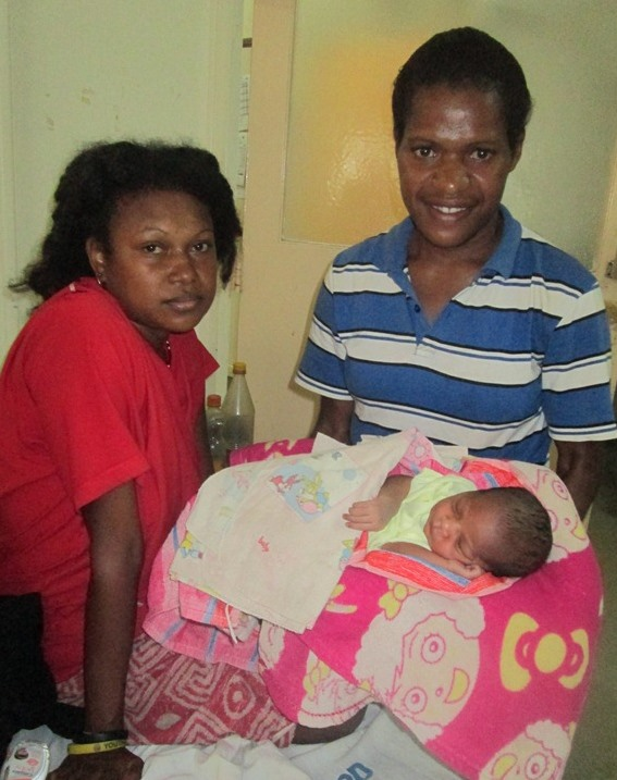 Mother Grace Tambor and student health extension officer Margaret Kalisi holding newborn baby girl
