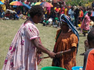 Mary Yuke exchanges gifts with Julie from Wau (orange blouse)