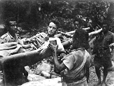 Private A Baldwin, 2 33 Battalion, receives a drink of water from Papuan stretcher-bearers, October 1942 [AWM]