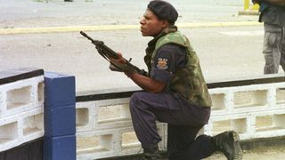 Riot policeman takes cover outside Murray Barracks in Port Moresby (Michael Bowers)