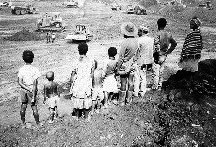 Pilipolo Oko and some family watch as their village is levelled to make way for the Porgera mine