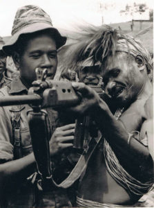 Private Simon showing his rifle to a Kukukuku tribesman