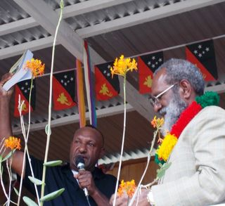 Jimmy Drekore and Hon Kerenga Kua MP show the crowd the PNG Anthology 2014