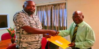 Justin (right) receives his letter of appointment from Governor Ereman ToBaining Jnr