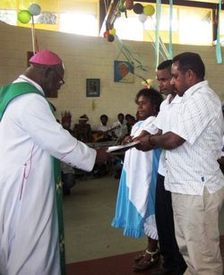 Bishop Otto Separi of Aitape hands a copy of the plan to a Goroka family