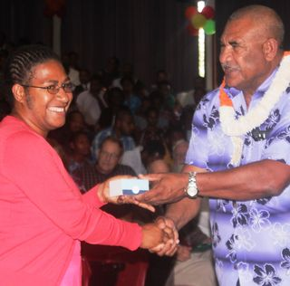 Mao Kali OBE, Secretary of the Department of Personnel Management, hands a cross to a student