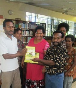 Bernard presents Anthology to Jartis Dedingi & Library staff