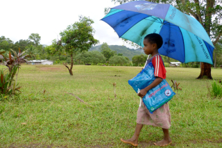 Girl carries home a bednet received during a distribution in Oro Province (Rotarians Against Malaria)