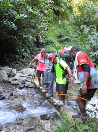 Adventure Kokoda carriers assist at a river crossing