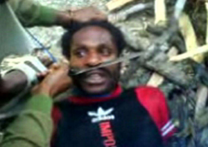 A terrified Papuan man is tortured with a machete by an Indonesian soldier