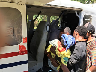 Loading the injured woman into the plane at Simogu (Dave Rogers)