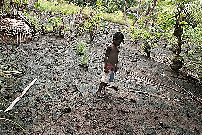 Mongabay - A young boy looks at mud contaminated by salt water (Jeremy Sutton  Greenpeace)