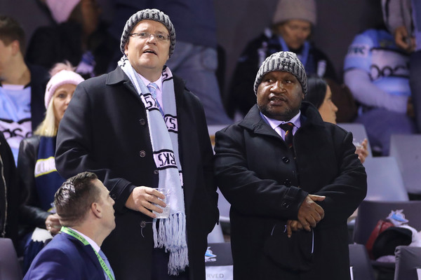 Scott Morrison and James Marape - beanie clad and doing the populist footie thing