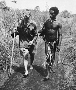 Anzac - Australian soldier Private George Whittington aided by Papuan orderly Raphael Oimbari  near Buna  25 December 1942 George Silk)