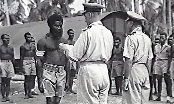 Lt Cdr Pryce-Jones  Intelligence Officer  Naval Intelligence Division (responsible for Coastwatchers) presents Loyal Services Medal to Sergeant Major Yauwiga  October 1943  Guadalcanal