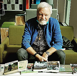 Dr Robie with books produced at PMC during his 13-year tenure (Laurens Ikinia)