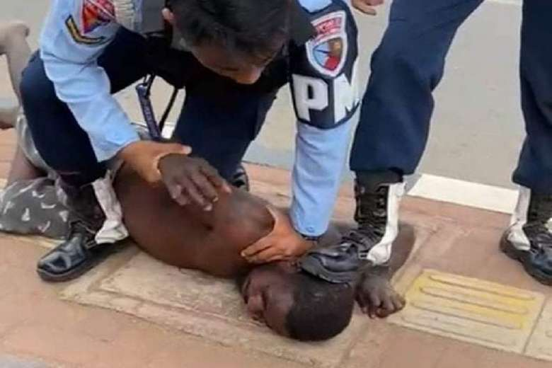 Two Indonesian Air Force officers assault a disabled Papuan man